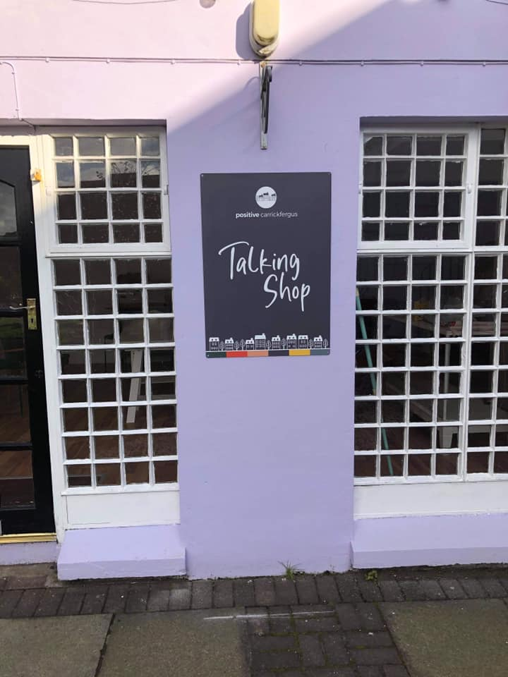 A picture of the Talking Shop sign on the wall outside the shop with windows either side