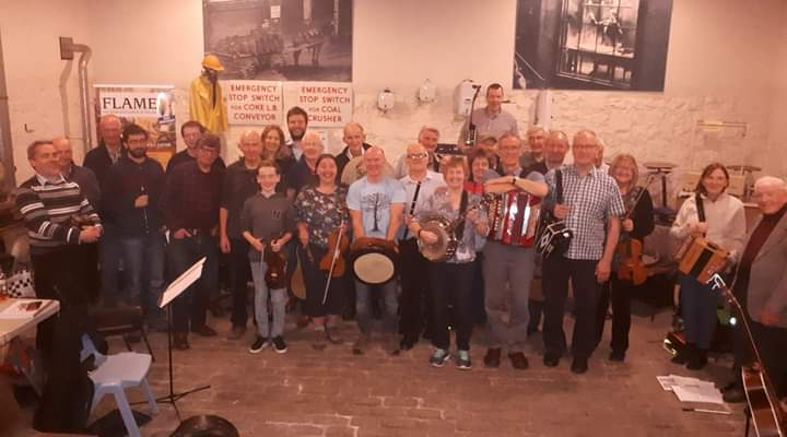 A group of musicians and their instruments stand together in Flame - a gasworks museum