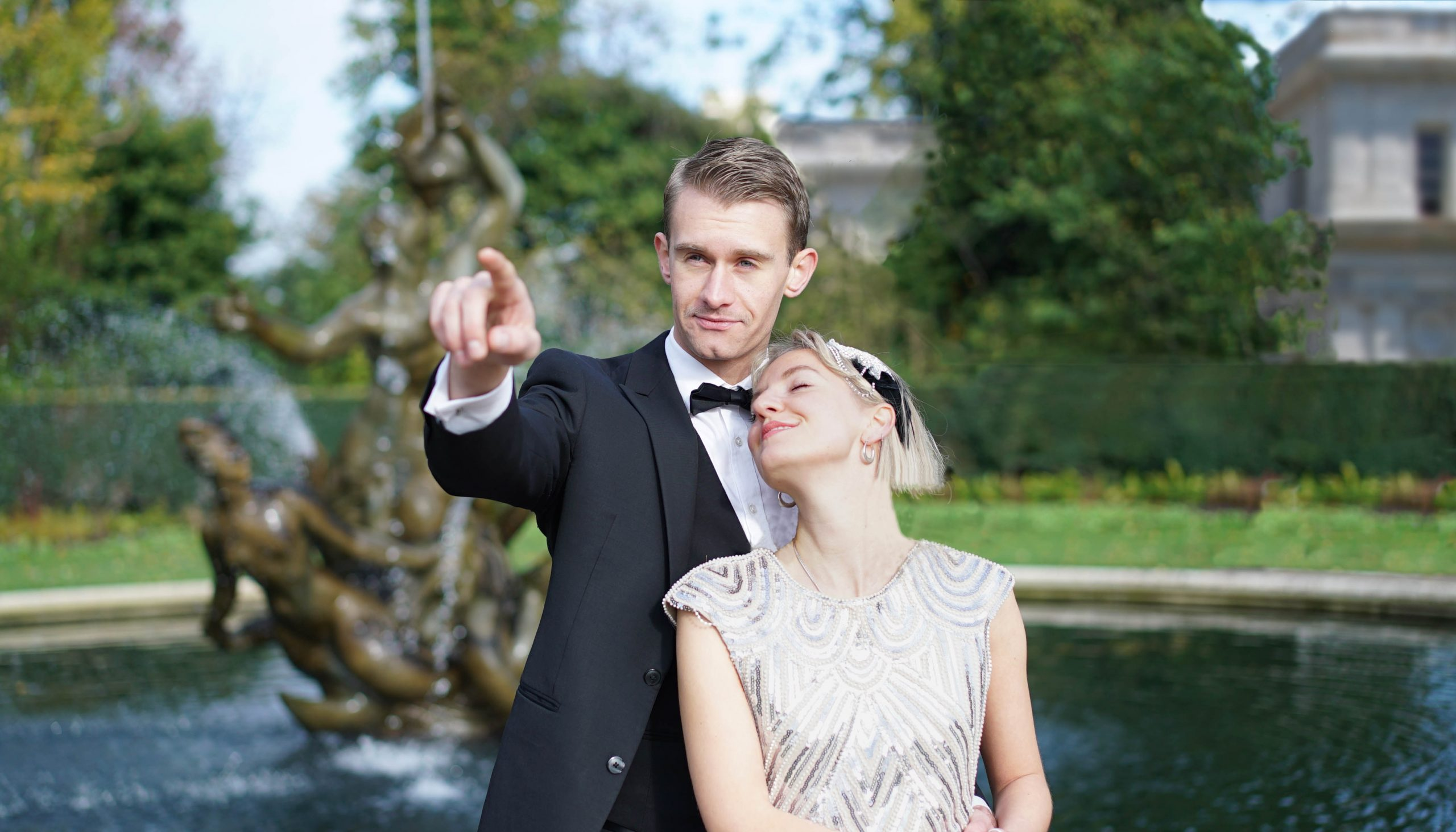 A woman in 1920's clothing leans back against a man in a tuxedo. They are both in a park