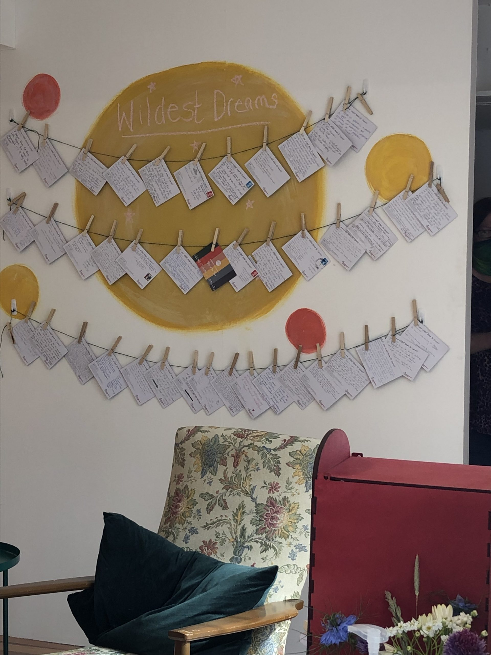 Lots of postcards attached to string by clothes pegs are displayed on a white wall with yellow and red spots
